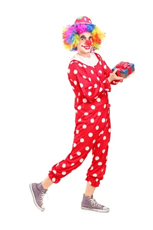 Full length portrait of a male clown with joyful expression on his face holding a gift isolated on white background Stock Photo - 17135451