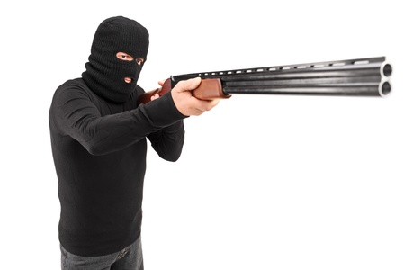 A man with robbery mask attacking someone with shotgun isolated on white background photo