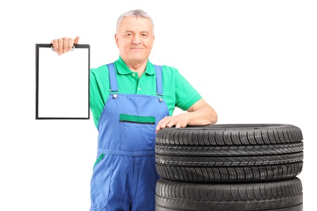 A mature worker on car tyres holding a clipboard isolated on white background photo