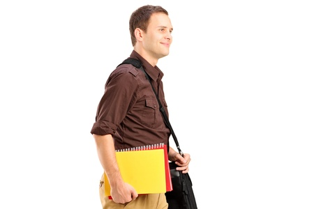 A male student with shoulder bag holding books and walking isolated on white background photo