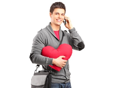 A smiling student holding a red heart and talking on a phone isolated on white background Stock Photo - 17167199