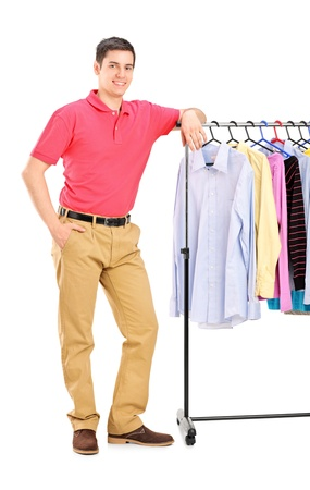 clothes rail: Full length portrait of a smiling guy posing on a hang rail full of clothes isolated on white background
