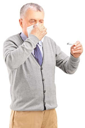 grippe: Ill senior man blowing his nose in tissue paper and looking at thermometer isolated on white background