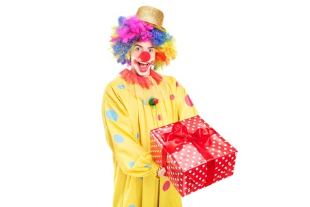 A happy male clown holding a red present isolated on white background Stock Photo - 17293658