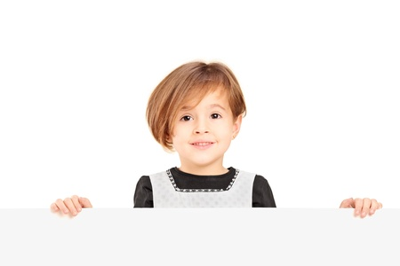 Little smiling girl standing behind a blank panel isolated on white background Stock Photo - 17279950