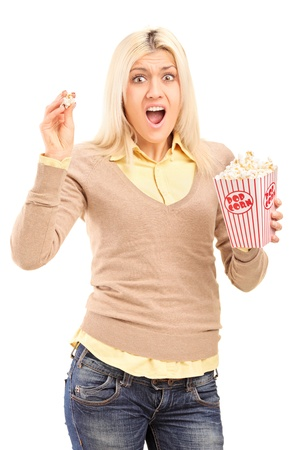 terrified: Scared blond woman holding a popcorn box and screaming isolated on white background