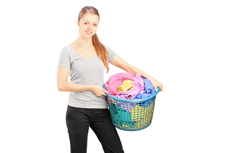 house wife: Young woman standing and holding a laundry basket full of clothes isolated on white background  Stock Photo