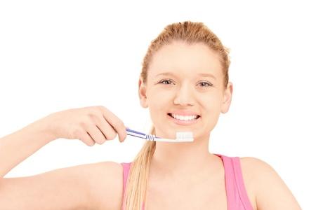 habitos saludables: Una hermosa mujer rubia cepillarse los dientes aislados en fondo blanco Foto de archivo