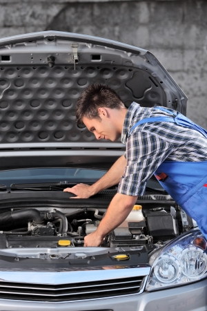 A young mechanic in overalls examining an automobile Stock Photo - 17321439