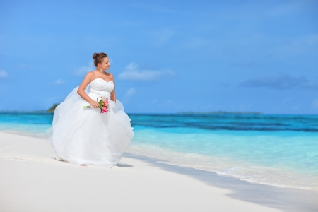 Bride watching towards the see on an exotic beach in Maldives photo