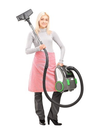 housemaid: Full length portrait of a blond housewife holding a vacuum cleaner isolated on white background