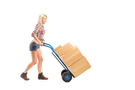 hand truck: Full length portrait of a female worker pushing a hand truck with boxes isolated on white background Stock Photo