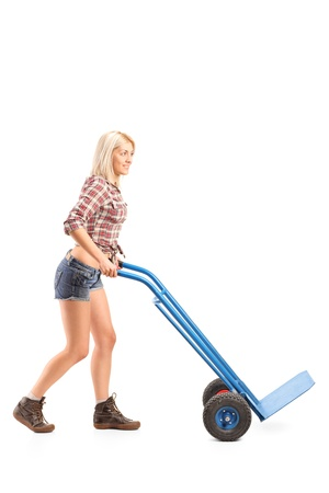 Full length portrait of a female worker pushing an empty hand truck isolated against white background photo