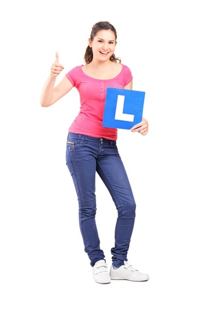 l plate: Full length portrait of a happy teenager holding L plate and giving a thumb up isolated against white background