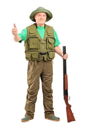 man holding gun: Full length portrait of a hunter holding a rifle and giving a thumb up isolated on white background