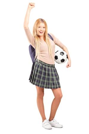 euphoric: Ritratto integrale di uno studente di euforico femminile con zaino in possesso di un pallone da calcio isolato su sfondo bianco
