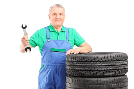 Mature mechanic standing with car tires and holding a wrench isolated on white background Stock Photo - 17321379