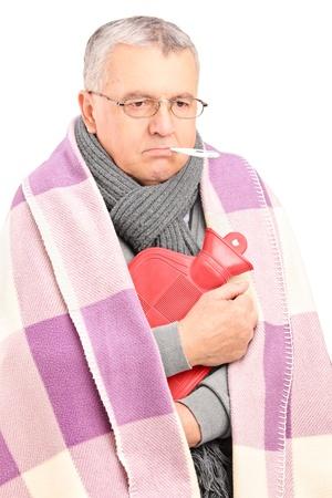 gripe: Enfermo mayor con term�metro en la boca, cubierto con la manta con una botella de agua caliente aisladas sobre fondo blanco