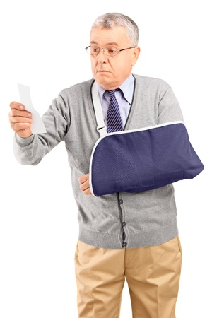 A surprised senior man with broken arm looking at receipt isolated on white background