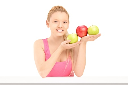 Young beautiful female sitting and holding three apples isolated on white background photo