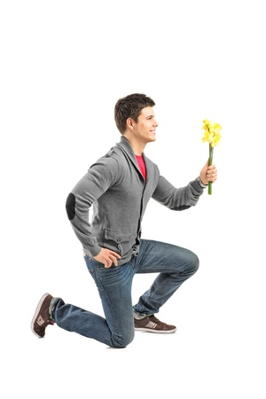 kneeling man: A male kneeling and holding a flower isolated on white background