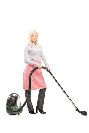 housemaid: Full length portrait of a blond housewife cleaning with a vacuum cleaner isolated on white background