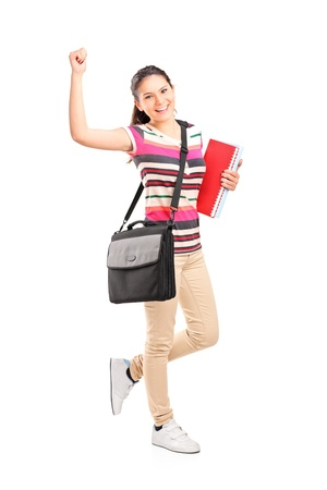 Full length portrait of a happy female student holding notebooks isolated on white background Stock Photo