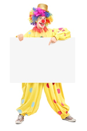 Full length portrait of a happy male clown pointing on a blank panel isolated on white background photo