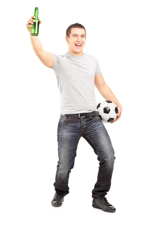 Full length portrait of an euphoric sport fan holding a beer bottle and football cheering isolated on white background