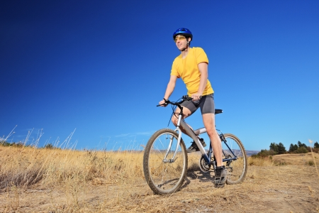 Panning shot of a bicycle rider riding a mountain bike outdoors on a sunny day against a blue sky photo