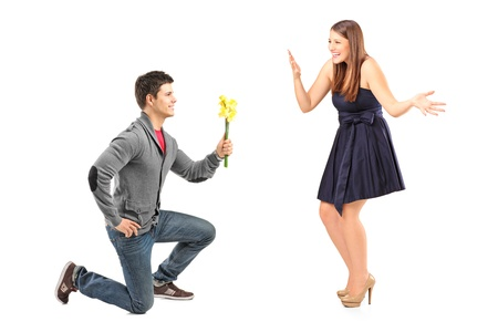 kneeling man: A male kneeling with flowers and his excited girlfriend isolated on white background