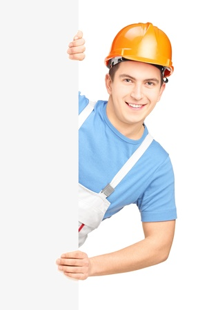 A male worker with helmet posing behind a blank panel isolated on white background Stock Photo - 17346106
