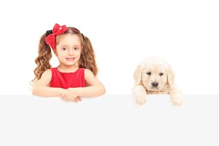 niños con pancarta: Un pequeño perro perdiguero labrador lindo muchacha y posando detrás de un panel en blanco aislado en fondo blanco