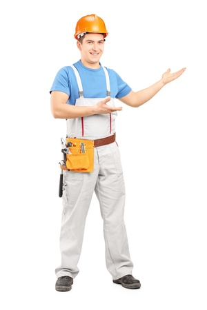 Full length portrait of a manual worker with tool belt and helmet gesturing isolated on white background Stock Photo - 17346102