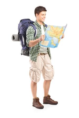 Pełna długość portret męskiej turystą patrząc na mapę, na białym tle
