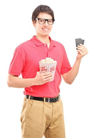 Young smiling man holding a popcorn box and two tickets for cinema isolated on white background photo