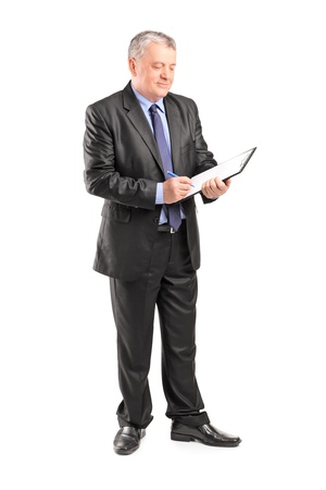 full suit: Full length portrait of a mature businessman looking at documents isolated on white background