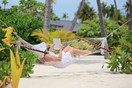 Woman relaxing in a hammock and reading a book on a beach in Maldives photo