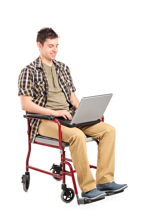 paralyze: Young disabled man in a wheelchair working on a laptop isolated on white background Stock Photo