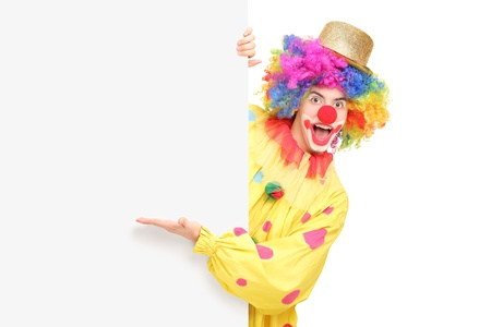 A funny circus clown posing behind a blank panel and gesturing isolated on white background Stock Photo - 17411203