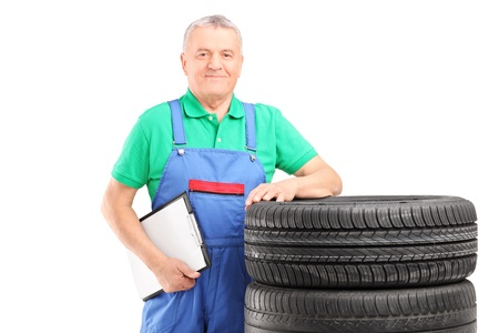 A mature worker posing on car tires with clipboard isolated on white background Stock Photo - 17411261