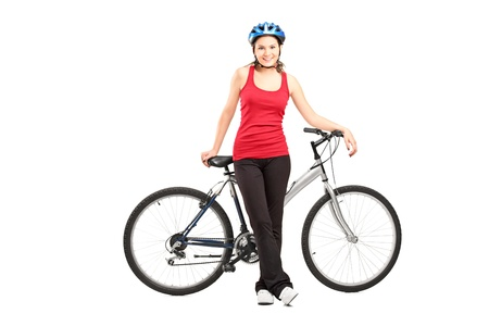 Full length portrait of a female biker with helmet posing next to a mountain bike isolated against white background Stock Photo - 17411195