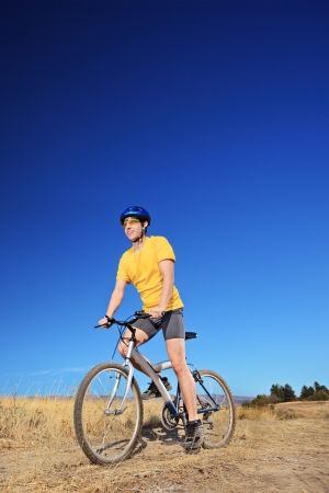 panning shot: Panning shot of a bicycle rider riding a bike outdoors on a sunny day against a blue sky Stock Photo