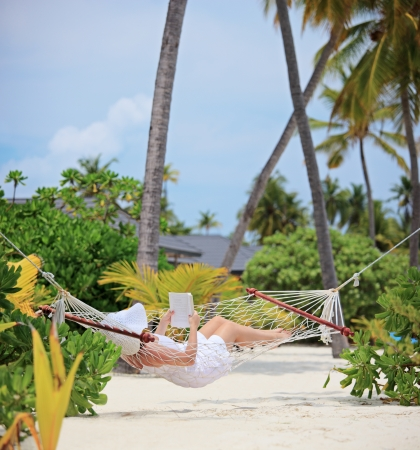pleasure of reading: Woman relaxing in a hammock and reading a book on a beach in Maldives, shot with a tilt and shift lens