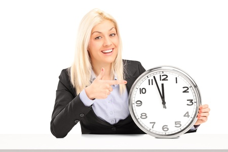 Blond businesswoman sitting and pointing on a wall clock, isolated on white background photo