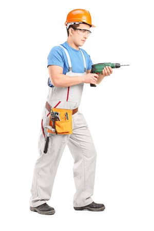 driller: Full length portrait of a manual worker with helmet using a drill tool isolated on white background Stock Photo