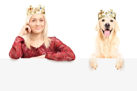 Royal female and dog wearing crowns and posing behind blank panel, isolated on white background photo