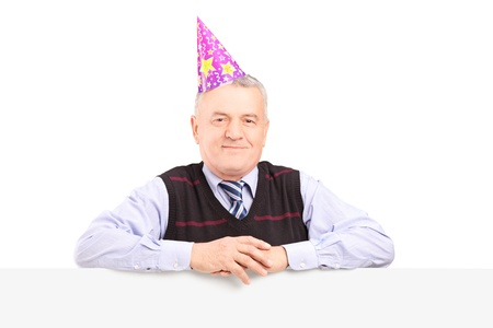Gentleman wearing party hat and posing behind a blank panel isolated on white background Stock Photo - 17495218