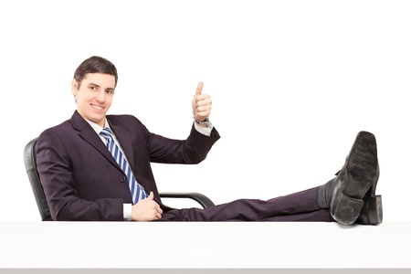 Young smiling businessperson sitting on a chair with his legs up and giving a thumb up isolated on white background photo