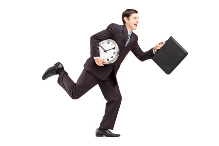late 20s: Full length portrait of a businessman running with clock and briefcase isolated on white background